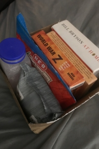 A small cardboard box full of audio books, nuts, and pills.
